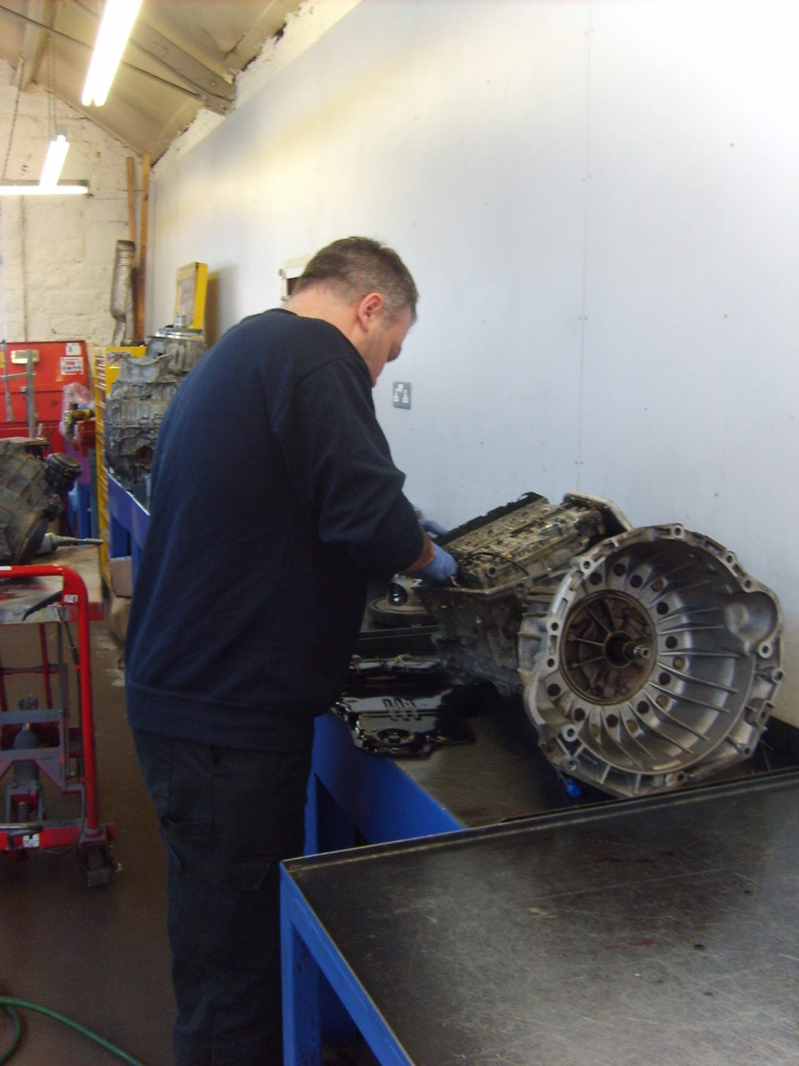 team member doing repair work at auto gear box